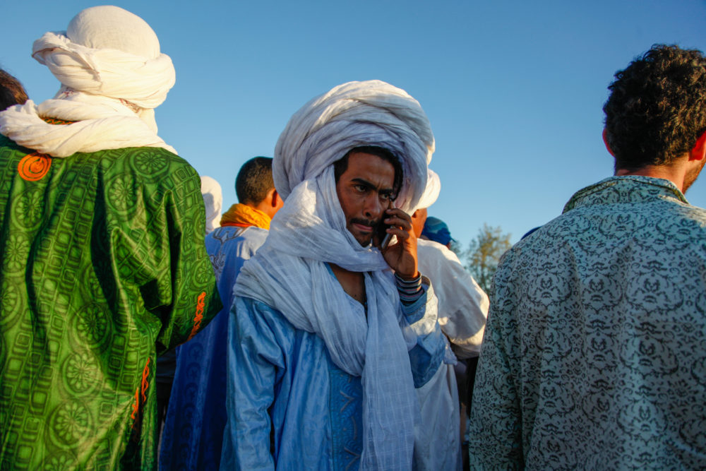 A festival attendee with gandoura, cheche, and cellphone.