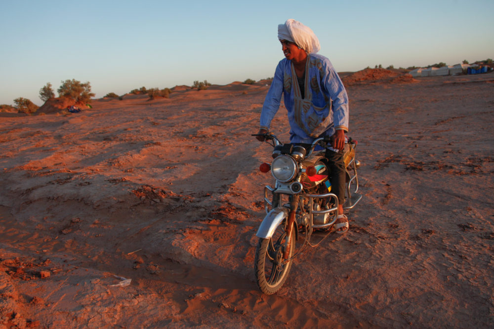 A young M'hamid local rides a motorcycle through the festival grounds.