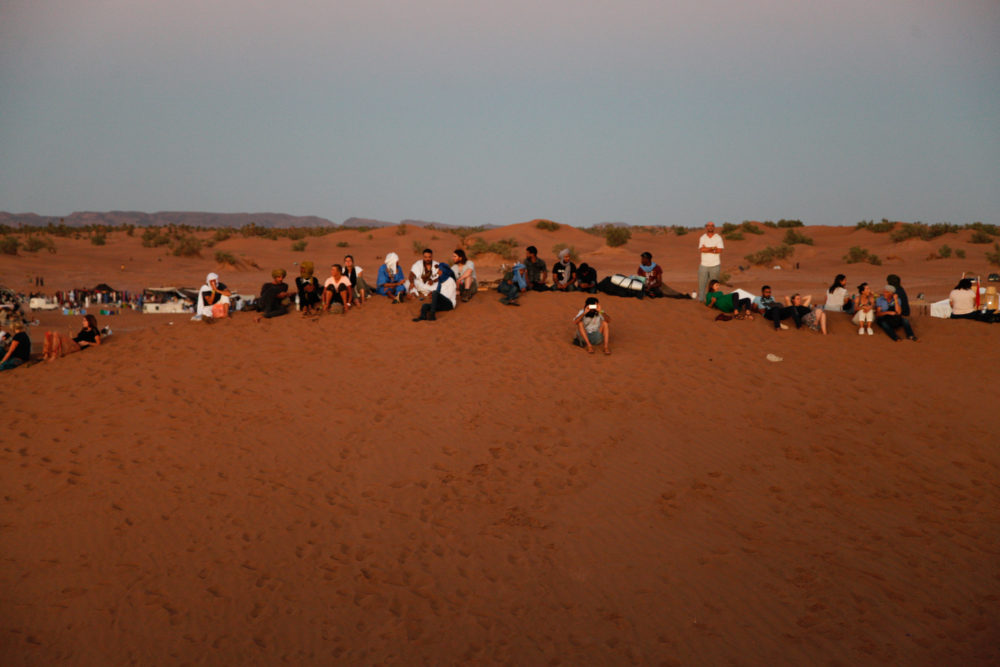 The festival crowd gathers for the sunset.