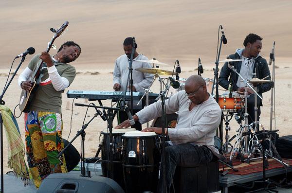 Elemotho Galelekwe and band making music in the dunes