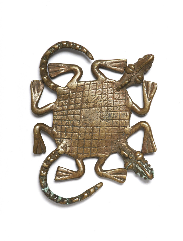 A gold-weight in the shape of a two-headed crocodile made in Ghana and used for weighing gold dust, made c 18th – 20th century and on display in West Africa: Word, Symbol, Song. The crocodile symbolizes cooperation and interdependence.