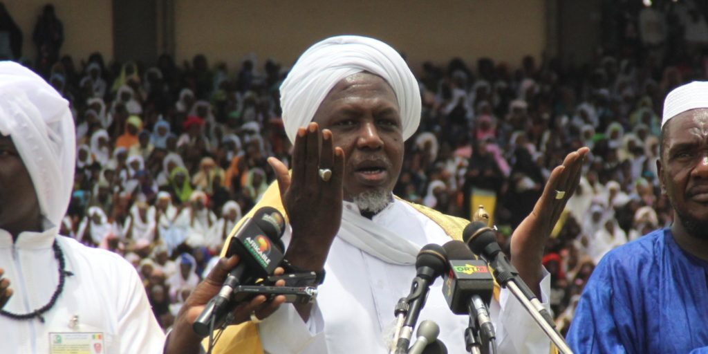 """Mahmoud Dicko (C), head of Mali's High Islamic Council prays on August 12, 2012 in Bamako during a giant peace rally in Mali. Up to 60,000 people gathered Sunday for a giant peace rally in Mali, a country split in two after Islamists wrested control of northern desert regions after a March coup in the capital Bamako. The meeting for """"national peace and reconciliation"""" in Bamako's main stadium was called by the country's top Muslim body and drew several key politicians including Prime Minister Cheikh Modibo Diarra. AFP PHOTO / HABIBOU KOUYATE (Photo credit should read HABIBOU KOUYATE/AFP/GettyImages)"""